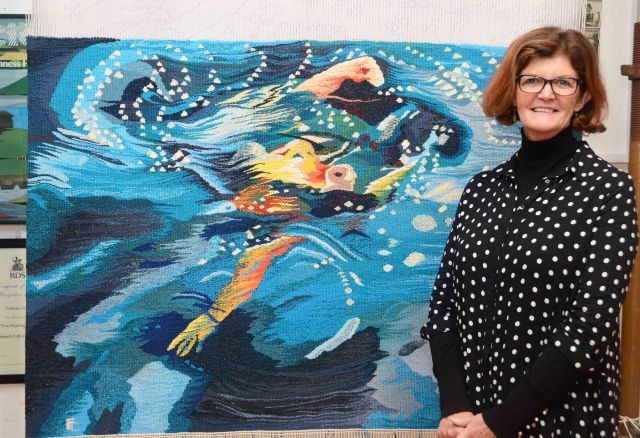 frances crowe in fornt of her latest tapestry titled Turmoil Measures 105 cm by 150 cm